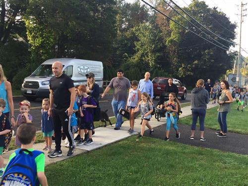Students and family members walk up the sidewalk to enter school