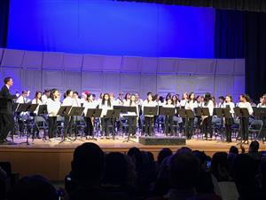 Middle School Band students stand as Don Whitman enters the stage